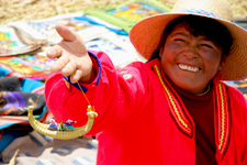 Puno cover photo. Smiling woman on one of the Floating Islan