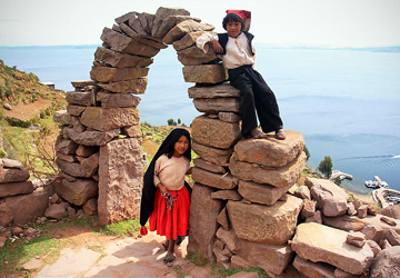 Peruvian children at the stone entry arch of Taquile Island.