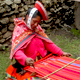 Traditionally dressed woman weaving in Cusco, Peru.