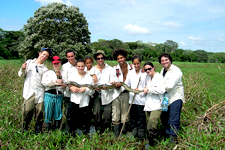 Group holding large boa snake in the marshlands of Bolivia.