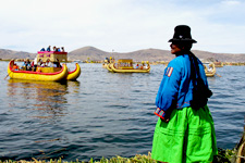 Woman looking over Lake Titicaca at reed boats of Uros near