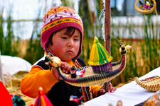 Girl with totora reed souvenier on Uros Island in Lake Titic