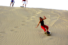 Girl sandboarding down large sand dunes near Huacachina oasi